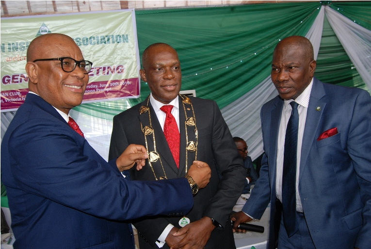 L-R: Immediate past chairman, Nigerian Insurance Association (NIA), Godwin Wiggle, decorating the Managing Director, Consolidated Hallmark Insurance Plc, Mr Eddie Efekoha, as new NIA Chairman, with Director General, NIA, Sunday Thomas, during the 45th Annual General Meeting of NIA held in Lagos on Thursday 30:6:2016.